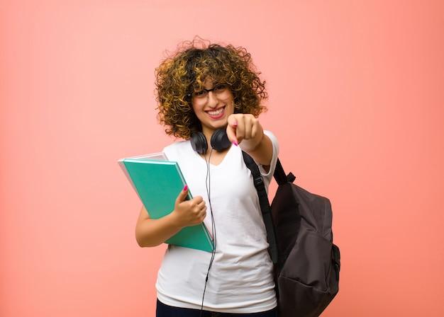 Joven estudiante bonita mujer apuntando a la cámara con una sonrisa satisfecha, segura y amigable, eligiéndote sobre la pared rosa
