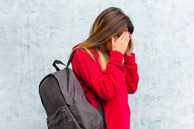 Joven estudiante bonita que cubre los ojos con las manos con una mirada triste y frustrada de desesperación, llanto, vista lateral