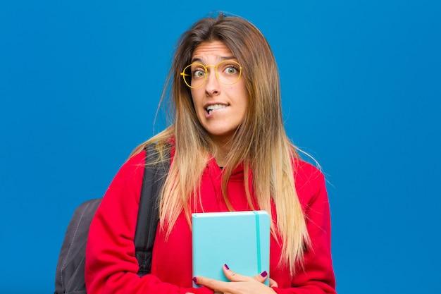 Joven estudiante bonita que parece confundida y confundida, mordiéndose el labio con un gesto nervioso, sin saber la respuesta al problema