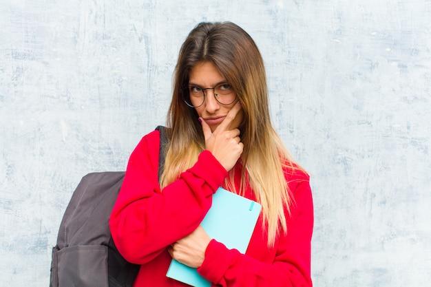 Joven estudiante bonita que parece seria, reflexiva y desconfiada, con un brazo cruzado y la mano en la barbilla, opciones de ponderación