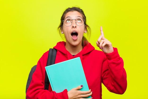 Joven estudiante bonita que parece sorprendida, con la boca abierta y apuntando hacia arriba con ambas manos para copiar el espacio
