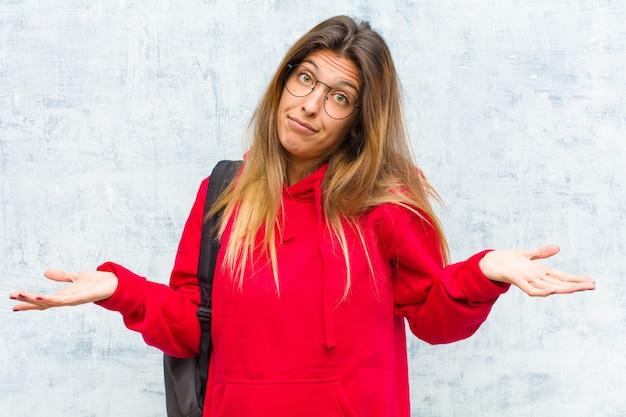 Joven estudiante bonita que se siente confundida y confundida, insegura sobre la respuesta o decisión correcta, tratando de tomar una decisión