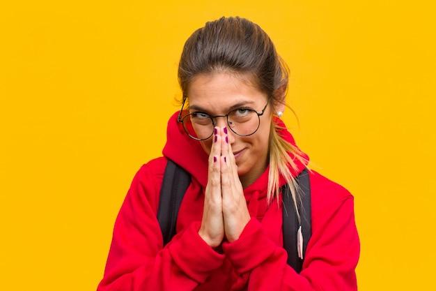 Joven estudiante bonita que se siente preocupada, esperanzada y religiosa, rezando fielmente con las palmas presionadas, pidiendo perdón