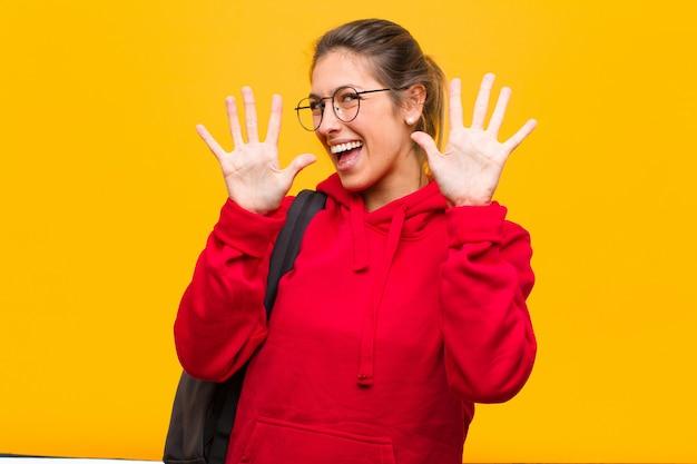 Joven estudiante bonita sonriendo y mirando amigable, mostrando el número décimo con la mano hacia adelante, contando hacia atrás