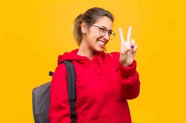 Joven estudiante bonita sonriendo y mirando amigable, mostrando el número dos o segundo con la mano hacia adelante, contando hacia atrás