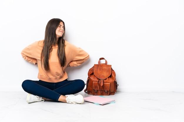 Joven estudiante brasileña sentada en el suelo sufriendo de dolor de espalda por haber hecho un esfuerzo