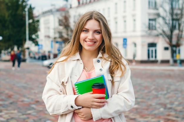 Una joven estudiante camina por la ciudad con una taza de café y un cuaderno. chica estudiante con cabello blanco
