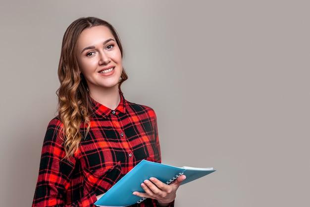 Una joven estudiante en una camisa a cuadros con cabello ondulado sostiene un cuaderno en una pared gris. chica estudiante realizando una encuesta de prueba.