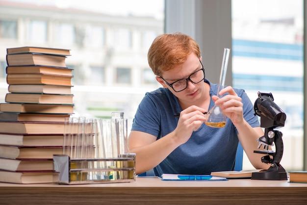 Joven estudiante cansado y agotado preparándose para el examen de química