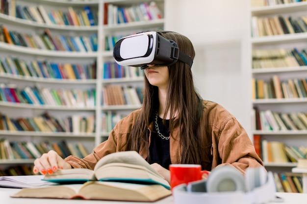 Joven estudiante caucásica en camisa marrón sentado en la mesa con libros en la biblioteca de la universidad y estudiando con gafas de realidad virtual