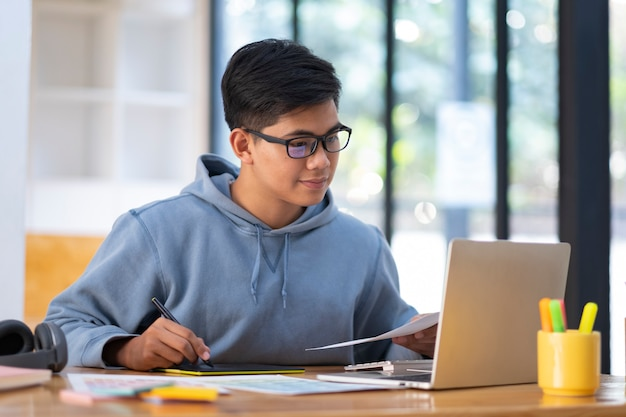 Joven estudiante de collage con computadora y dispositivo móvil estudiando en línea.