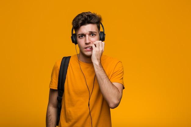 Joven estudiante cool hombre escuchando música con auriculares cruzando los dedos para tener suerte