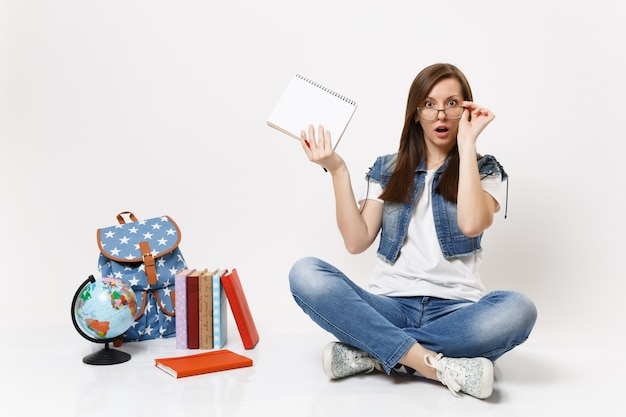 Joven estudiante desconcertado conmocionado manteniendo la mano en las gafas sostenga el cuaderno lápiz sentado cerca de la mochila del globo, libros escolares aislados