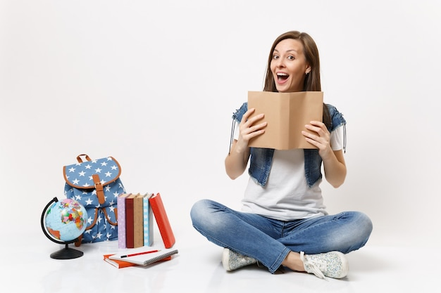 Joven estudiante divertida sorprendida en ropa de mezclilla con libro leyendo sentado cerca del globo, mochila, libros escolares aislados