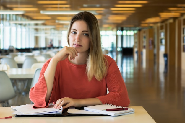 Joven estudiante estudiando en la biblioteca.