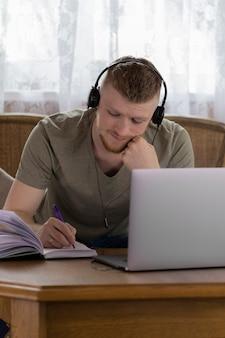 Un joven estudiante está estudiando en la universidad de forma remota desde casa usando una computadora portátil