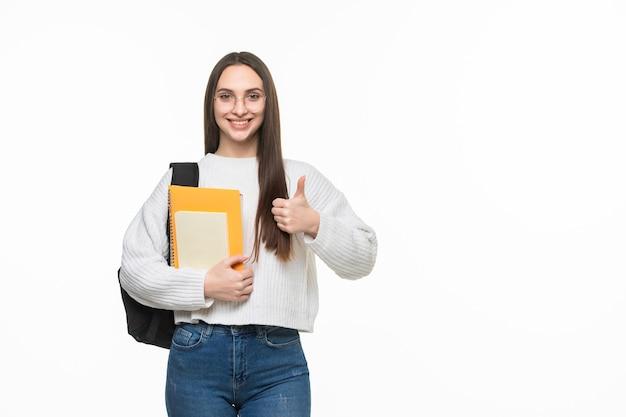 Joven estudiante feliz mostrando los pulgares para arriba aislado en la pared blanca