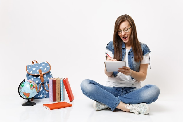 Joven estudiante feliz sorprendida en gafas escribiendo notas en el cuaderno sentado cerca del globo, mochila, libros escolares aislados