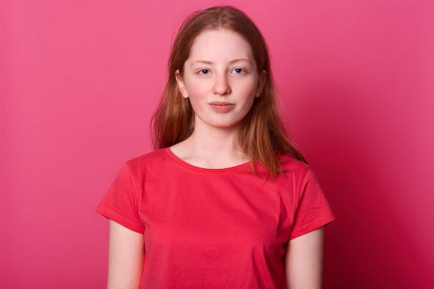 La joven estudiante femenina de medio cuerpo se ve con una expresión facial tranquila, con una camiseta roja informal, tiene el pelo largo y castaño y ojos azules, aislados en rosa
