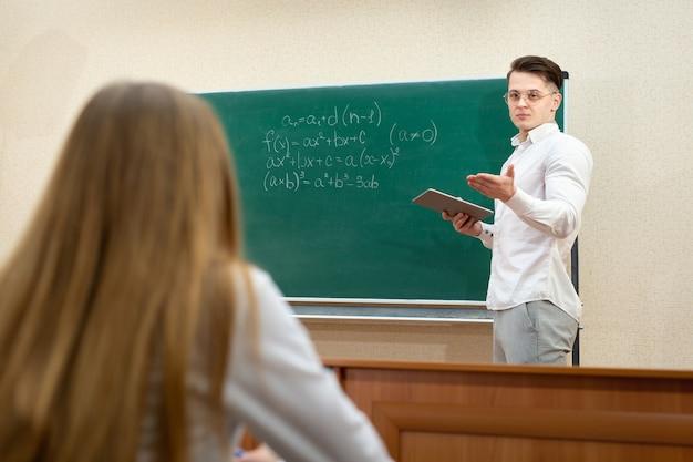 Joven estudiante con gafas y una tableta responde en la pizarra.