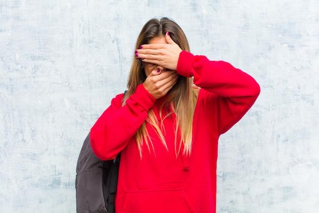 Joven estudiante guapa cubriéndose la cara con ambas manos diciendo no a la cámara! rechazar fotos o prohibir fotos