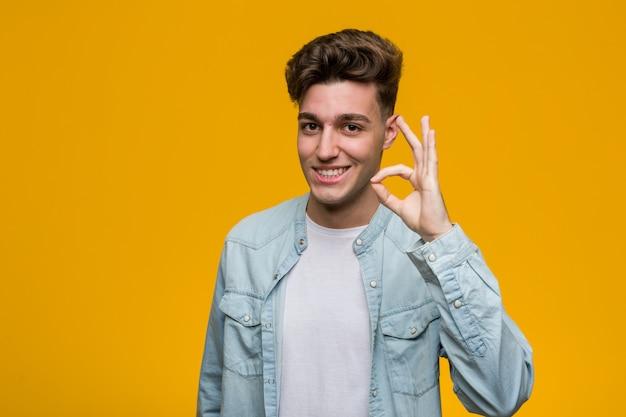 Joven estudiante guapo con una camisa de mezclilla alegre y confidente que muestra gesto bien.
