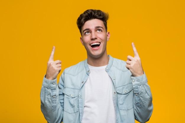 Joven estudiante guapo con una camisa de mezclilla indica con ambos dedos delanteros hacia arriba mostrando un espacio en blanco.