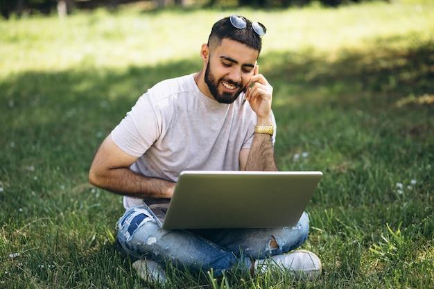 Joven estudiante guapo con computadora portátil en un parque de la universidad