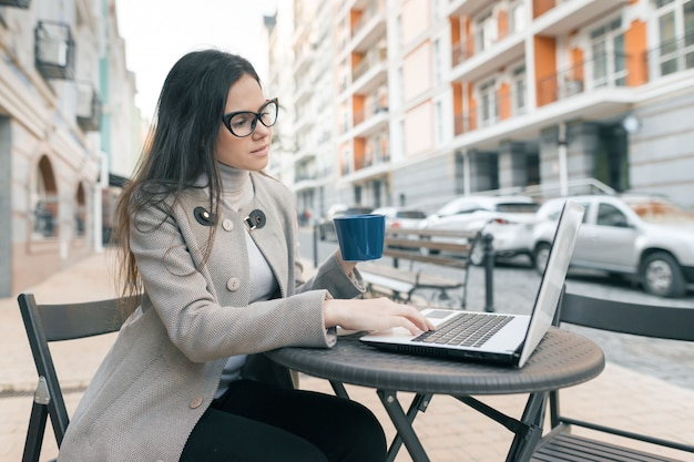 Joven estudiante hermosa en un café al aire libre con laptop