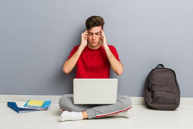 Joven estudiante hombre sentado en el piso de su casa sosteniendo una computadora portátil