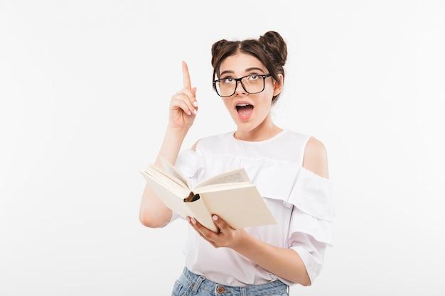 Joven estudiante inteligente o colegiala con peinado de bollos dobles y aparatos dentales apuntando con el dedo hacia arriba mientras lee el libro, aislado en blanco