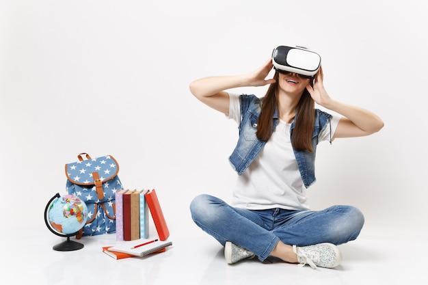 Joven estudiante interesada con gafas de realidad virtual disfrutando de juegos sentados cerca del globo, mochila, libros escolares aislados