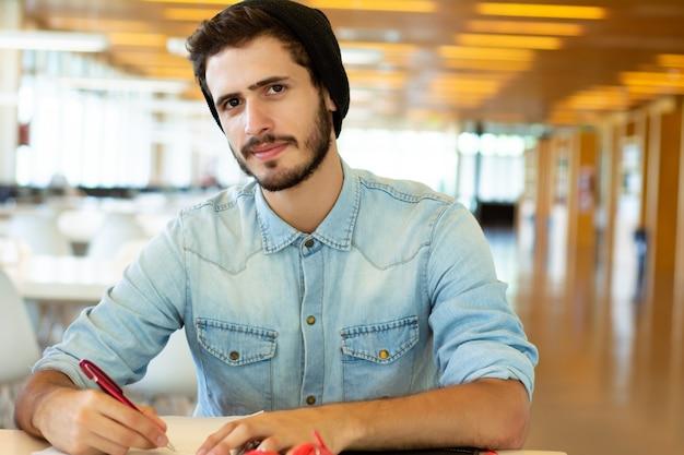 Joven estudiante masculino estudiando en la biblioteca.