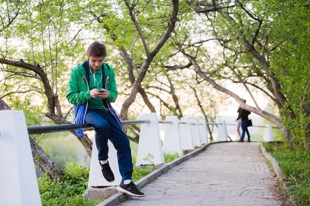Joven estudiante masculino sentado en el parque al atardecer tocar teléfono móvil escuchando música. luz suave y color vintage.