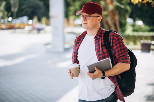 Joven estudiante masculino tomando café con el portátil en el parque
