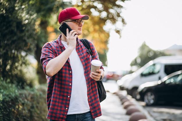 Joven estudiante masculino tomando café usando el teléfono en el parque