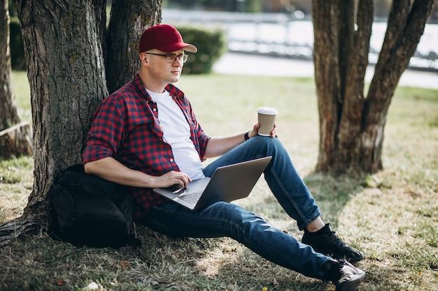 Joven estudiante masculino trabajando en una computadora en el parque