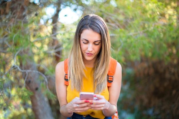 Joven estudiante con mochila al aire libre hablando con el móvil