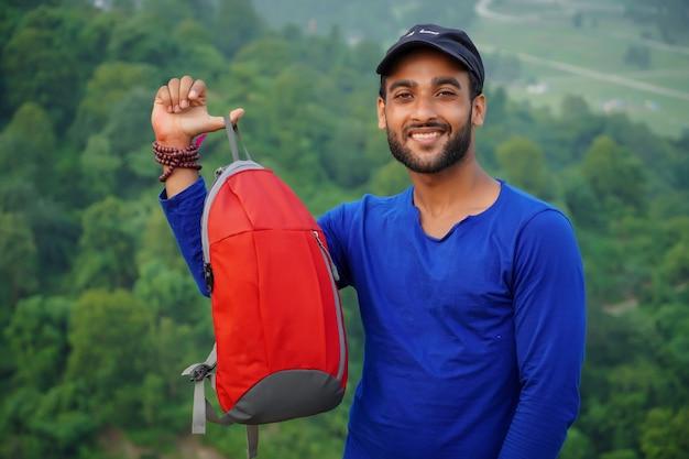 Un joven estudiante mostrando su bolso.