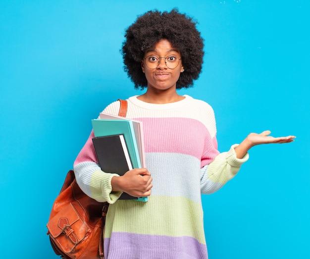 Joven estudiante mujer afro que se siente desconcertada y confundida, dudando, ponderando o eligiendo diferentes opciones con expresión divertida