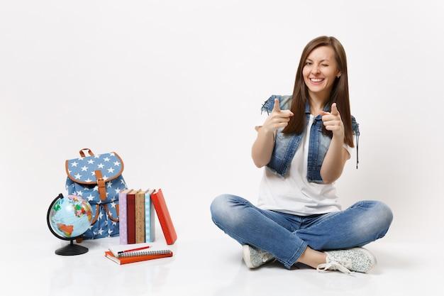 Joven estudiante mujer alegre en ropa de mezclilla parpadeando con el dedo índice apuntando a la cámara sentado cerca de libros de escuela de mochila globo aislado