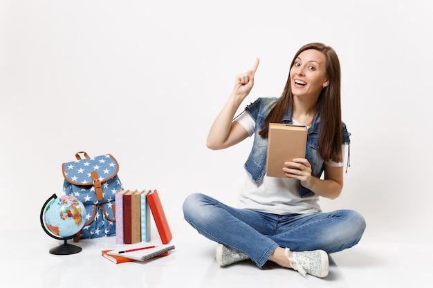 Joven estudiante mujer alegre en ropa de mezclilla sosteniendo libro apuntando con el dedo índice hacia arriba sentado cerca del globo, mochila, libros escolares aislados