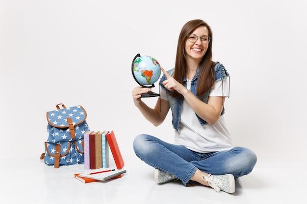Joven estudiante mujer alegre en vasos sosteniendo globo terráqueo dedo acusador en países sentados cerca de mochila, libros escolares aislados