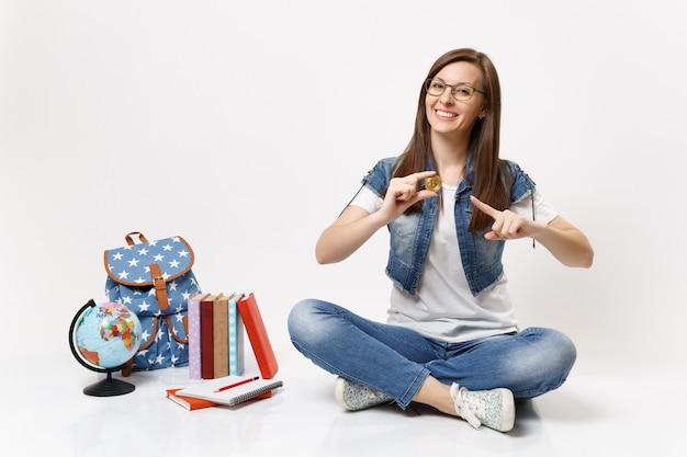 Joven estudiante mujer bonita alegre con gafas apuntando con el dedo índice en bitcoin sentarse cerca del globo, mochila, libros escolares aislados