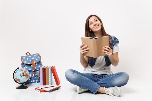 Joven estudiante de mujer bonita en ropa de mezclilla soñando mirando hacia arriba sosteniendo el libro sentado cerca de los libros escolares de la mochila del globo aislado