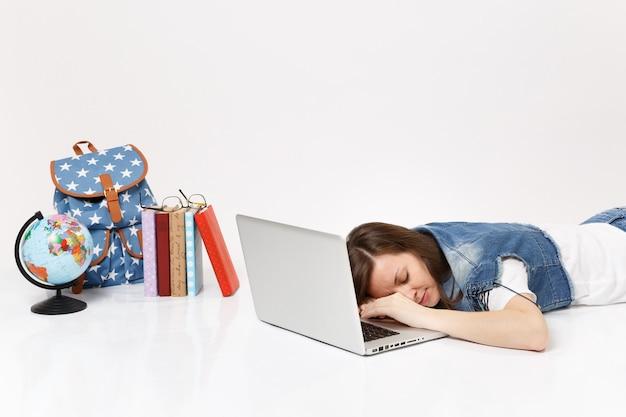 Joven estudiante mujer cansada en ropa de mezclilla durmiendo en la computadora portátil acostado cerca de la mochila del globo y los libros escolares