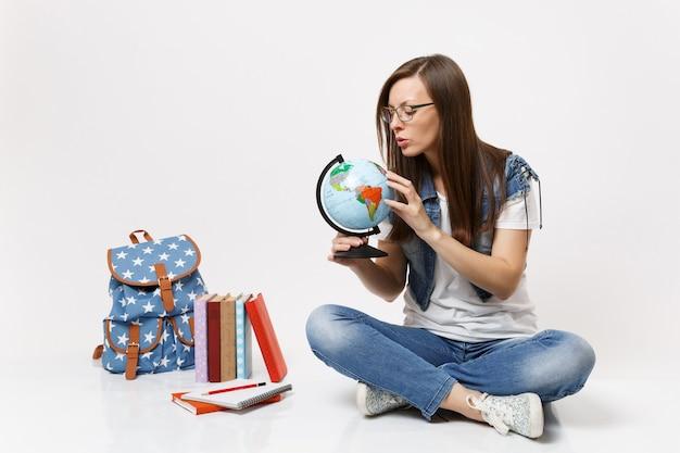 Joven estudiante mujer concentrada sosteniendo el globo del mundo buscando aprender sobre países sentados cerca de la mochila, libros escolares aislados