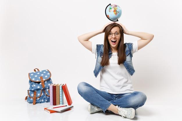 Joven estudiante mujer divertida alegre casual en vasos con globo del mundo en la cabeza sentado cerca de la mochila, libros escolares aislados