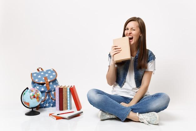 Joven estudiante mujer divertida loca en ropa de mezclilla sosteniendo morder libro royendo sentado cerca de libros de escuela de mochila de globo