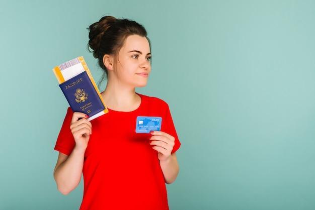 Joven estudiante mujer emocionada sonriente con pasaporte boleto de embarque y tarjeta de crédito